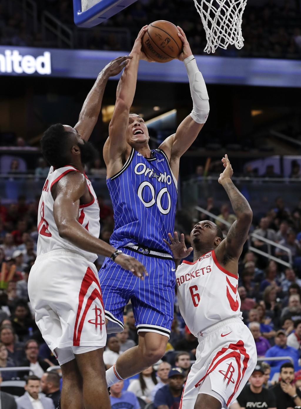 Orlando Magic's Aaron Gordon (00) shoots as he gets between Houston Rockets' James Harden, left, and Gary Clark (6) during the second half of an NBA b