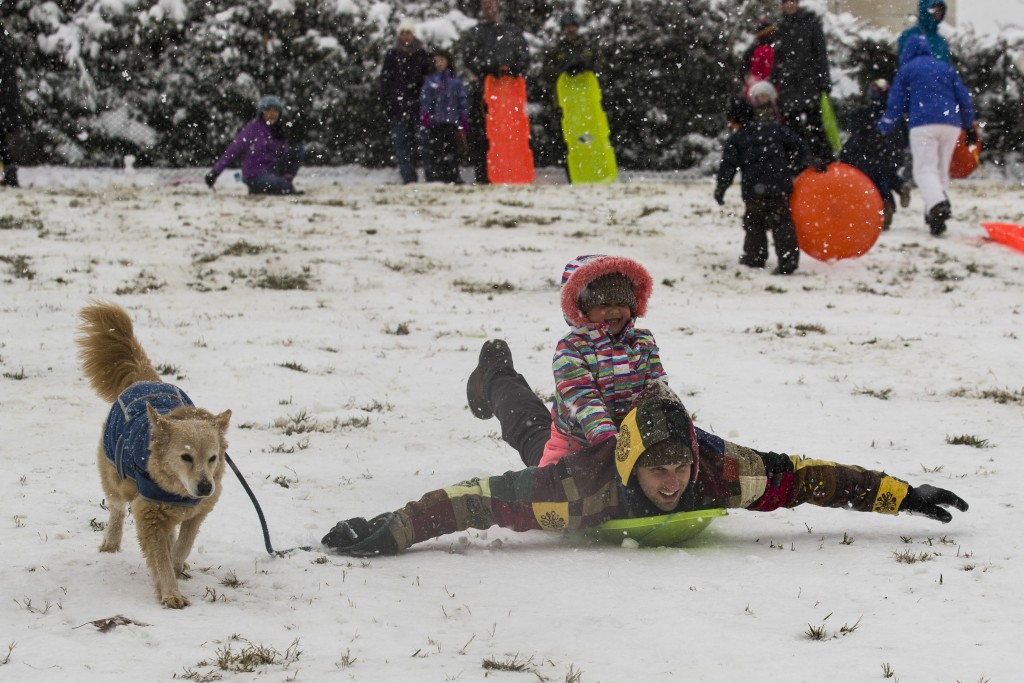 Jeremy Binstock gives his niece Olivia Binstock, 4, a sled ride as he hangs onto his dog Bagel, on Capitol Hill as a winter storm arrives in the regio
