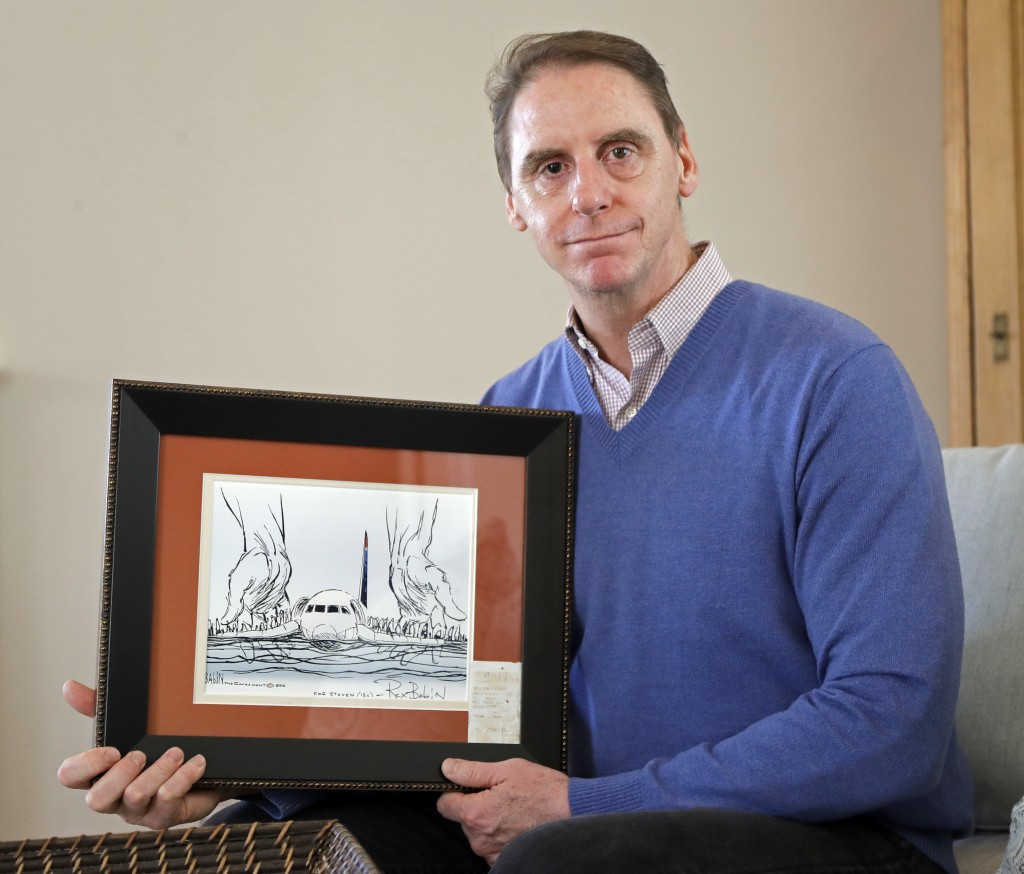 In this Jan. 10, 2019 photo, Steve O'Brien poses for a photo at his home in Charlotte, N.C.,  with an editorial cartoon framed with his boarding pass