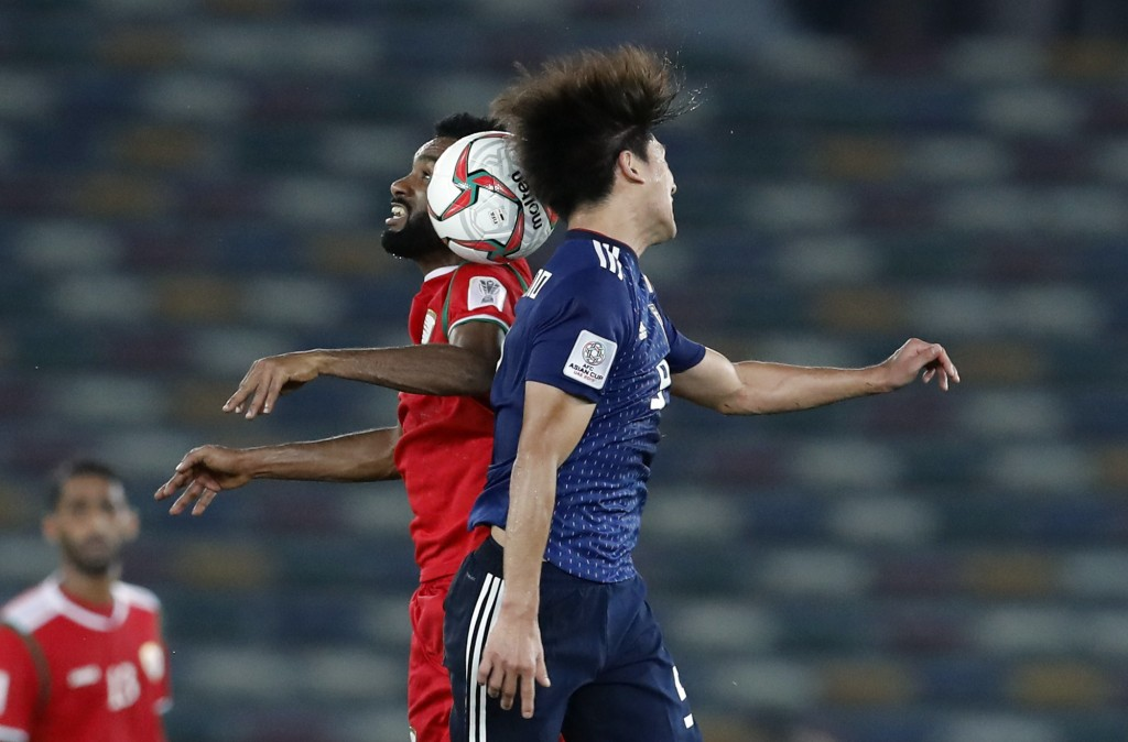 Japan's forward Takumi Minamind, right, is airborne with Oman's midfielder Harib Al-Saadi during the AFC Asian Cup group F soccer match between Japan