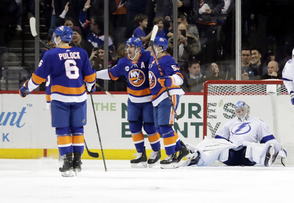 Tampa Bay Lightning goaltender Andrei Vasilevskiy, right, reacts as the New York Islanders celebrate a goal by Cal Clutterbuck during the first period