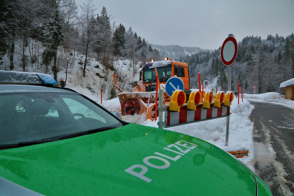 A police car blocks the street leading to Balderschwang as a snow plough passes by in Obermaiselstein, southern Germany, Monday, Jan. 14, 2019. (Benja