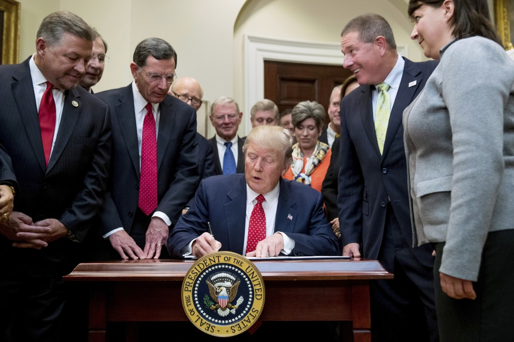 FILE - In this Tuesday, Feb. 28, 2017, file photo, President Donald Trump signs the Waters of the United States (WOTUS) executive order, in the Roosev