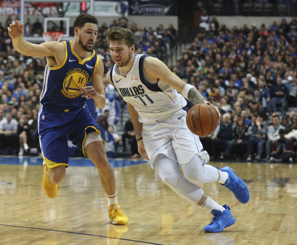 Golden State Warriors guard Klay Thompson (11) defends as Dallas Mavericks guard Luka Doncic (77) drives past in the second half of an NBA basketball ...
