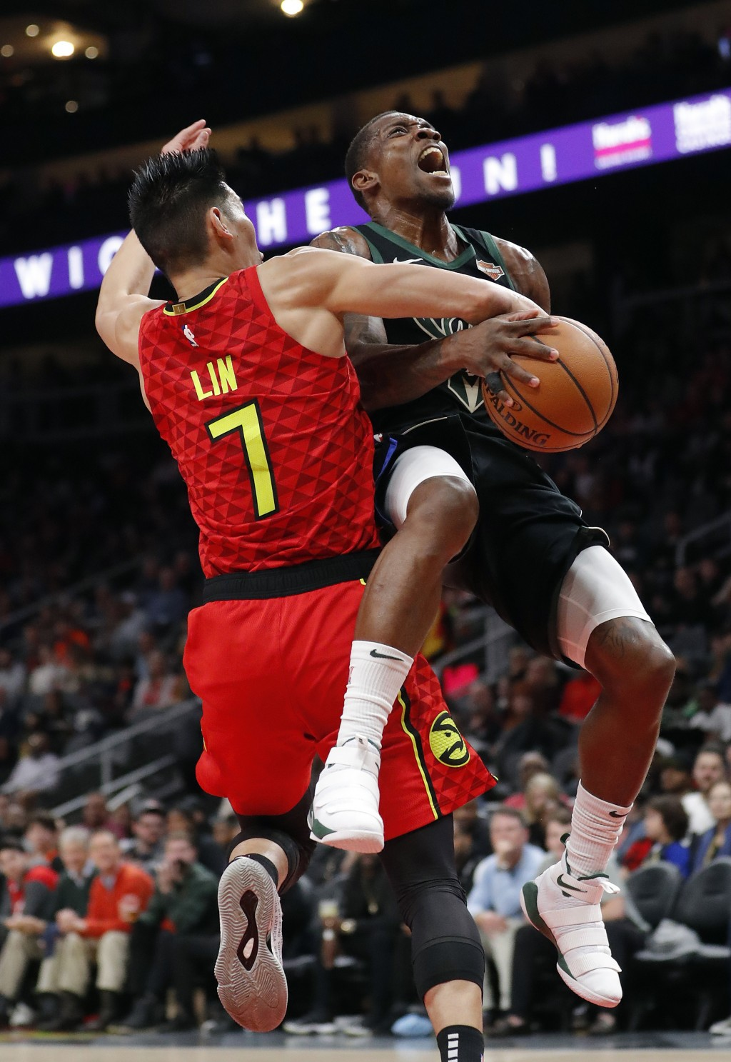 Milwaukee Bucks guard Eric Bledsoe, right, is fouled by Atlanta Hawks guard Jeremy Lin (7) in the first half of an NBA basketball game Sunday, Jan. 13