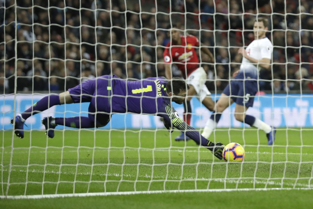 Tottenham goalkeeper Hugo Lloris fails to stop a shot on goal by Manchester United's Marcus Rashford, rear in red shirt, who scored his side's first g