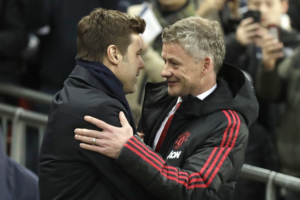 Manchester United caretaker manager Ole Gunnar Solskjaer, right, greets Tottenham manager Mauricio Pochettino, left, prior to the English Premier Leag