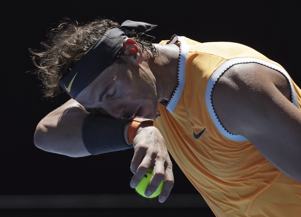Spain's Rafael Nadal wipes the sweat from his face as he serves to Australia's James Duckworth against during their first round match at the Australia