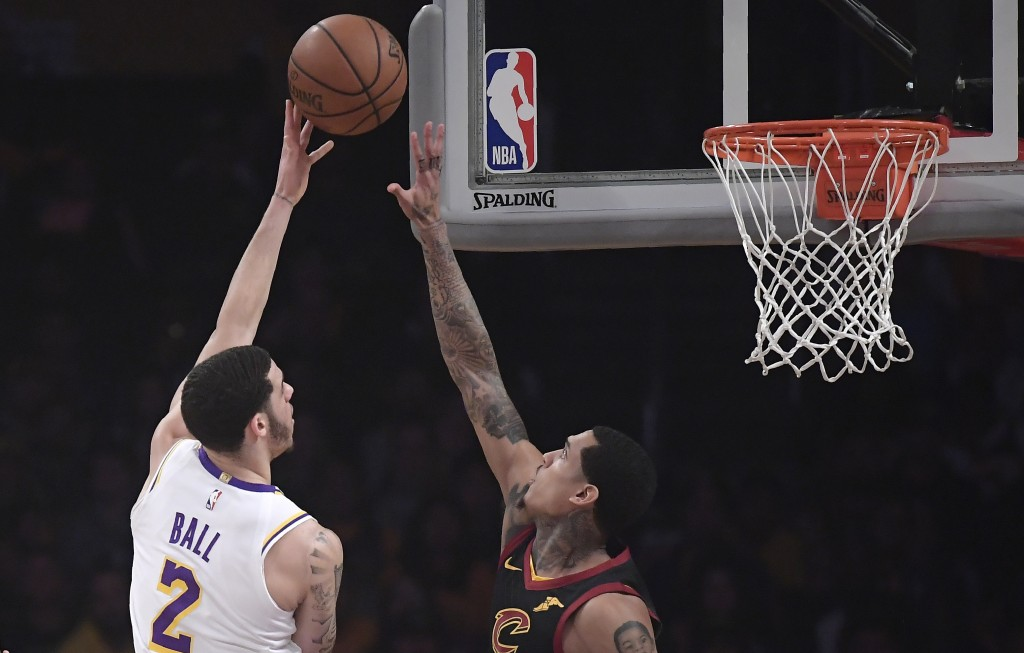 Los Angeles Lakers guard Lonzo Ball, left, shoots as Cleveland Cavaliers guard Jordan Clarkson defends during the first half of an NBA basketball game