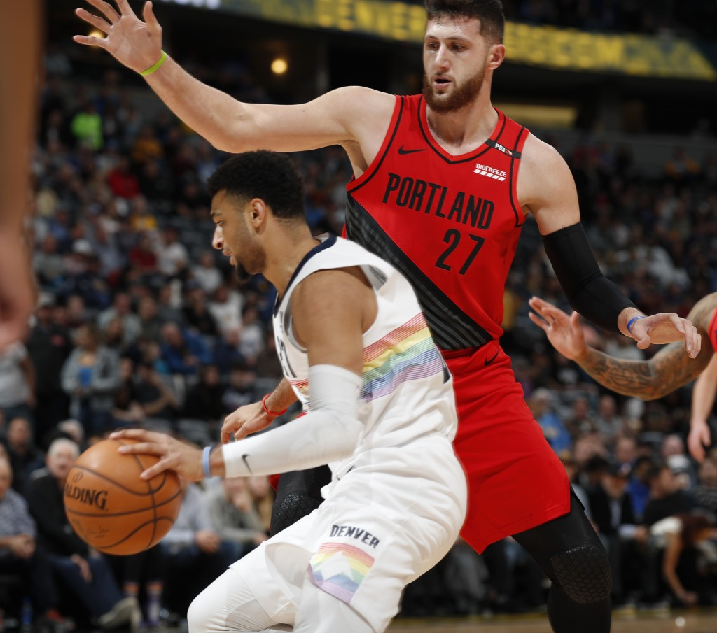 Denver Nuggets guard Jamal Murray, left, travels under the arm of Portland Trail Blazers center Jusuf Nurkic as he blocks the lane in the first half o