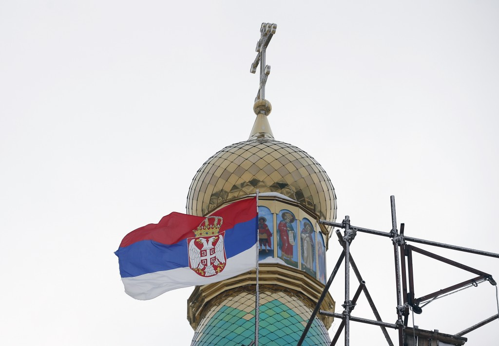 In this photo taken Friday, Jan. 11, 2019, the Serbian flag flies near a new church under construction designed in the Russian style in the village Ba...