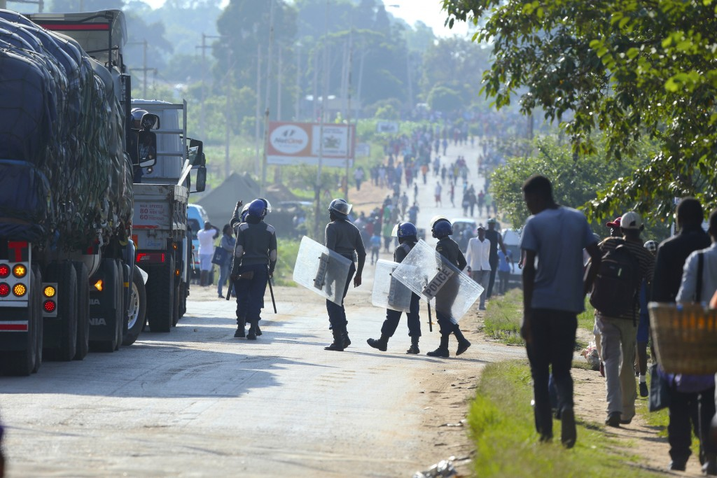 Riot police are seen on a street during a demonstration over the hike in fuel prices in Harare, Zimbabwe, Monday, Jan. 14, 2019. Zimbabwean President