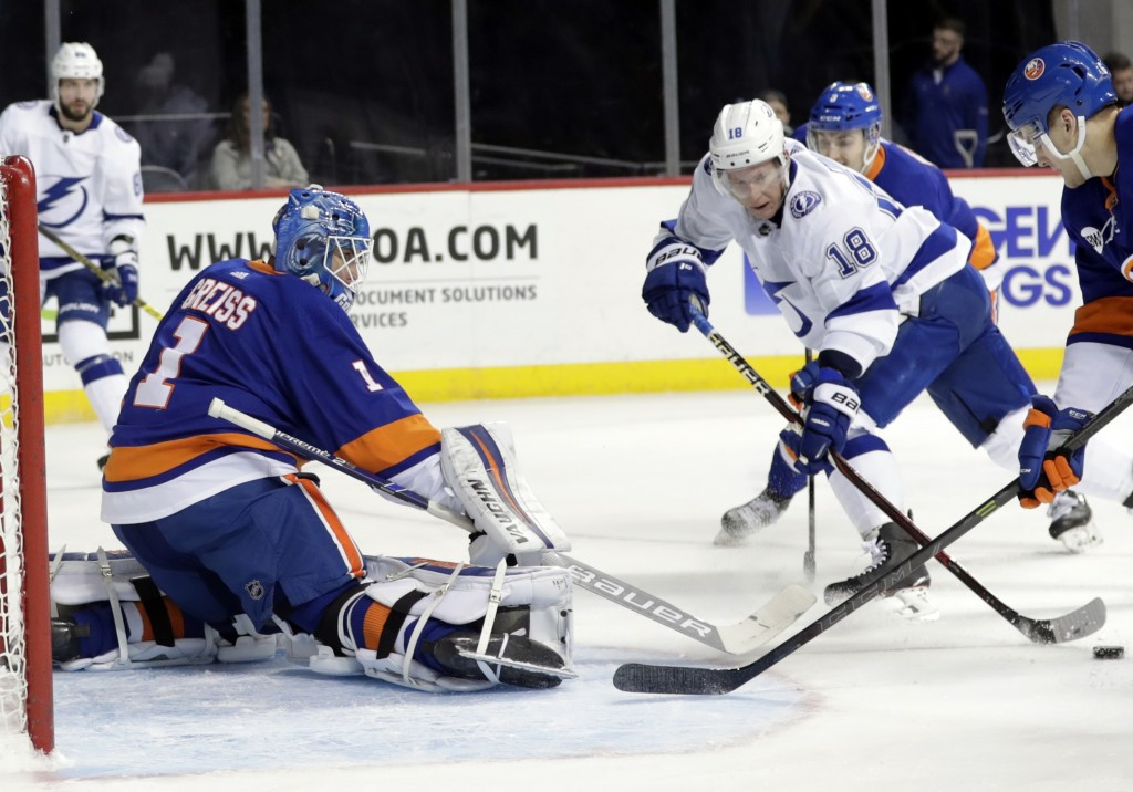 Tampa Bay Lightning's Ondrej Palat (18) attempts to score as New York Islanders goaltender Thomas Greiss (1) defends during the first period of an NHL