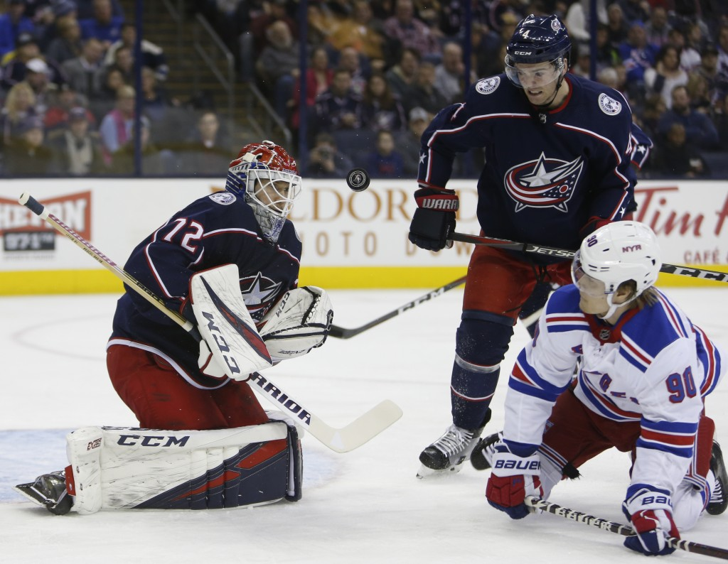 Columbus Blue Jackets' Sergei Bobrovsky, left, of Russia, makes a save in front of teammate Scott Harrington, center, and New York Rangers' Vladislav