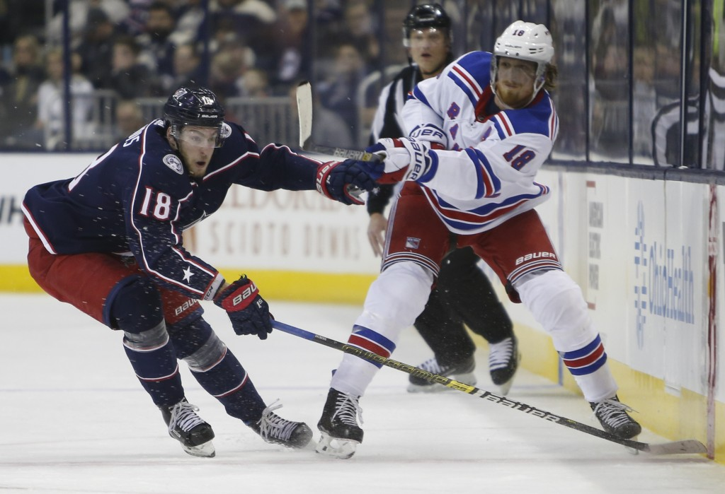 New York Rangers' Marc Staal, right, passes the puck in front of Columbus Blue Jackets' Pierre-Luc Dubois during the first period of an NHL hockey gam