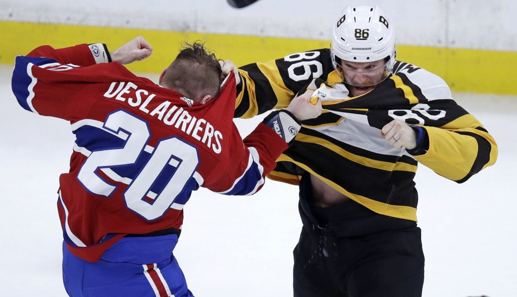 Boston Bruins defenseman Kevan Miller, right, fights Montreal Canadiens left wing Nicolas Deslauriers (20) during the first period of an NHL hockey ga
