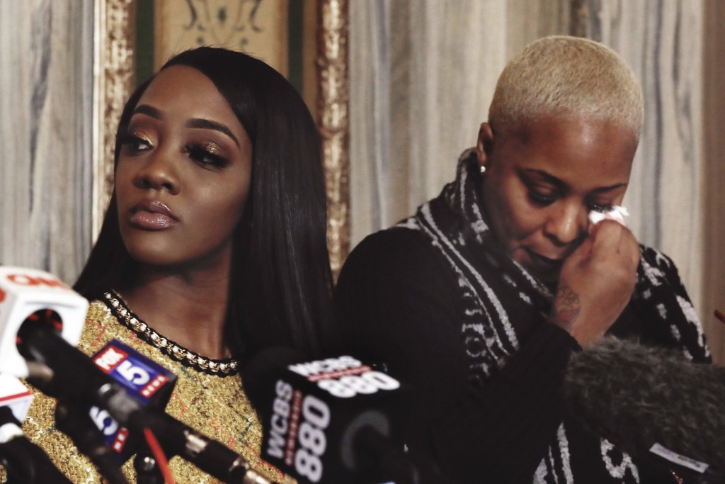 Faith Rodgers, left, listens during a news conference, as Michelle Kramer, mother of Dominique Gardner, wipes her eye after giving her statement about...