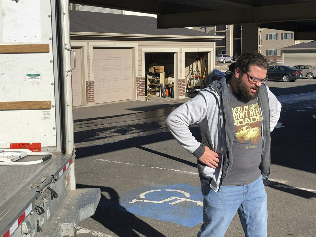 George Jankowski, a furloughed U.S. Department of Agriculture worker, helps a friend move out of an apartment in Cheyenne, Wyo., Monday, Jan. 14, 2019