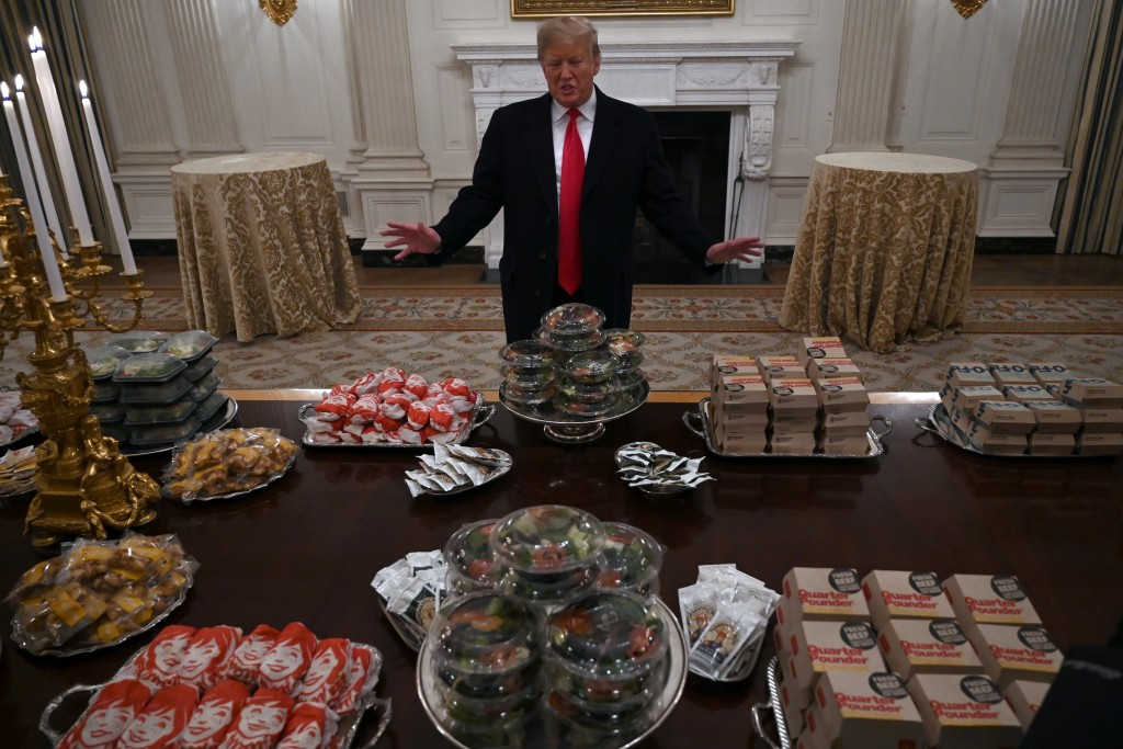 In this Jan. 14, 2019 photo, President Donald Trump talks to the media about the table full of fast food in the State Dining Room of the White House i