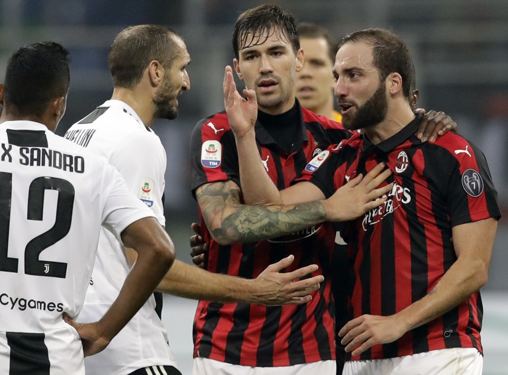 FILE - In this Nov. 11, 2018 file photo, AC Milan's Gonzalo Higuain, right, talks with Juventus' Giorgio Chiellini, during a Serie A soccer match betw...