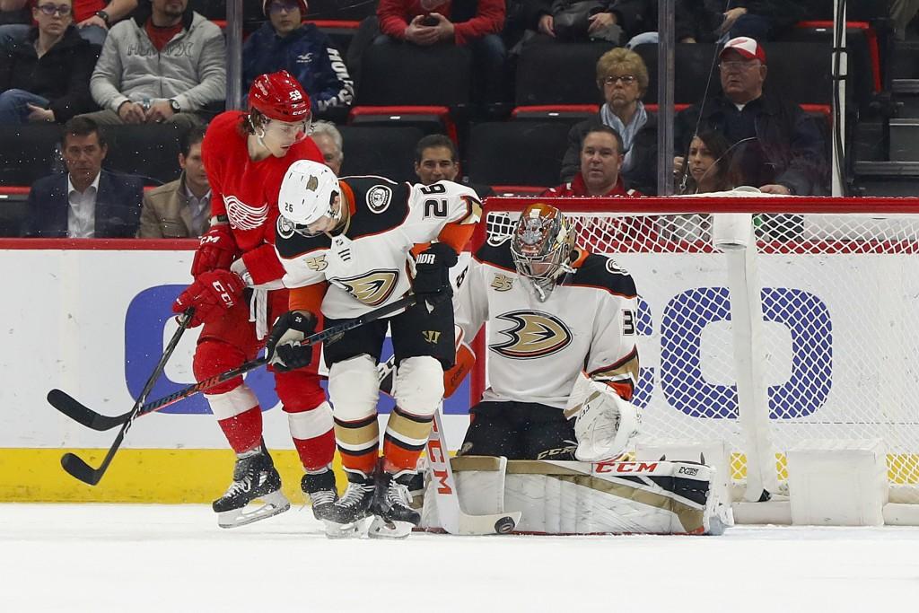 Anaheim Ducks goaltender John Gibson (36) stops a shot as Detroit Red Wings left wing Tyler Bertuzzi (59) and Anaheim Ducks defenseman Brandon Montour...