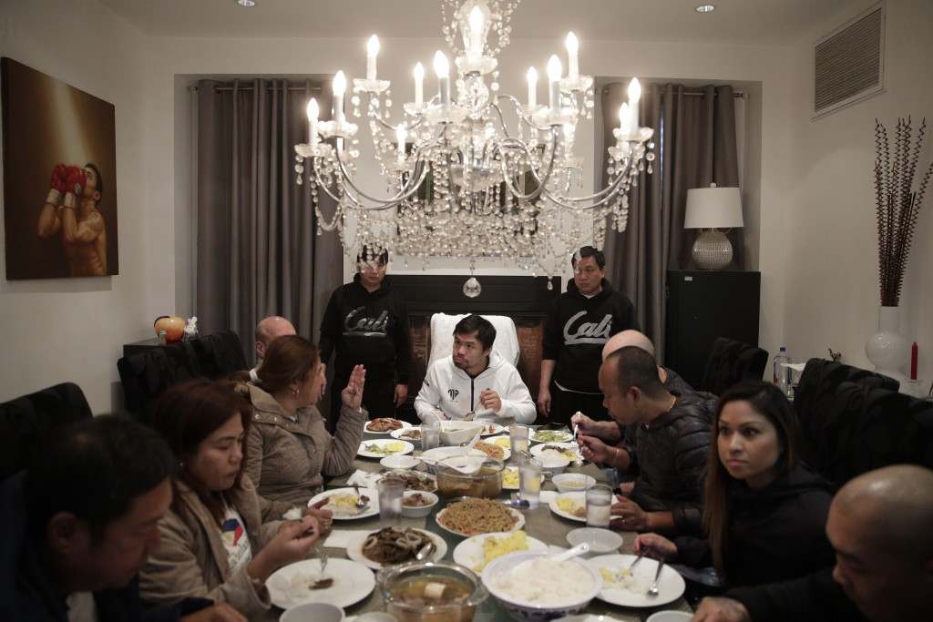 Boxer Manny Pacquiao, center, eats his breakfast with friends and relatives following his morning run Monday, Jan. 14, 2019, in Los Angeles. Breakfast