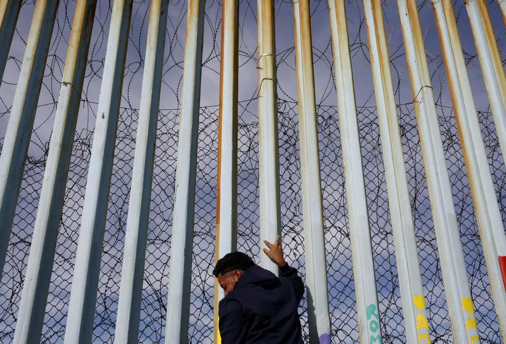 FILE - In this Jan. 8, 2019, file photo, a man holds on to the border wall along the beach, in Tijuana, Mexico. The migrant caravan that was seized up
