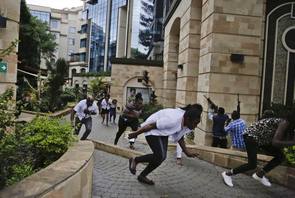Civilians flee as security forces aim their weapons at the buildings of a hotel complex in Nairobi, Kenya, Tuesday, Jan. 15, 2019. Extremists launched