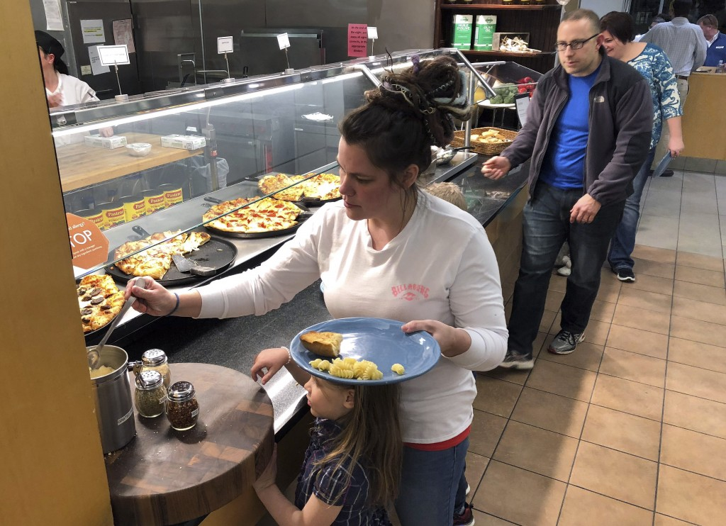 U.S. Coast Guard spouse Rachel Malcom, left, gathers food for herself and her daughter, Tuesday, Jan. 15, 2019, at Roger Williams University in Bristo