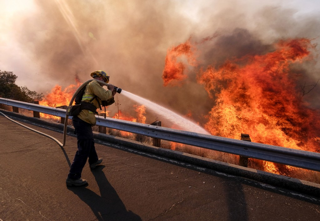 In this Nov. 12, 2018 file photo a firefighter battles a fire along the Ronald Reagan Freeway, aka state Highway 118, in Simi Valley, Calif. A group o