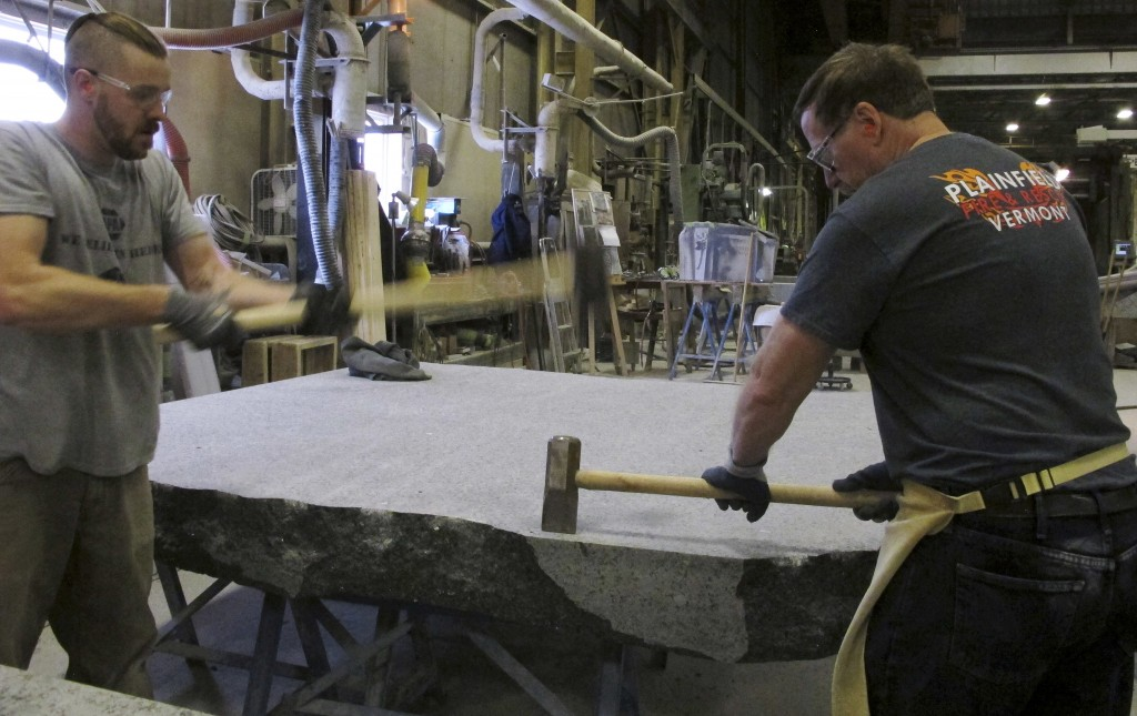 In this Tuesday, Jan. 8, 2019 photo, stone cutters Evan Ladd, left, and Andy Hebert cut a piece of granite at Rock of Ages in Barre, Vt. The granite w...