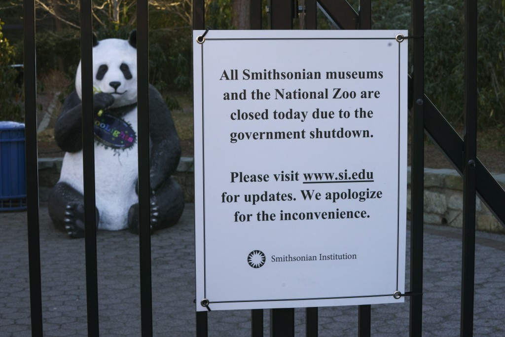 In this Friday, Jan. 11, 2019, photo a statue of a panda bear is seen behind the closed gate of the Smithsonian's National Zoo that is closed because ...