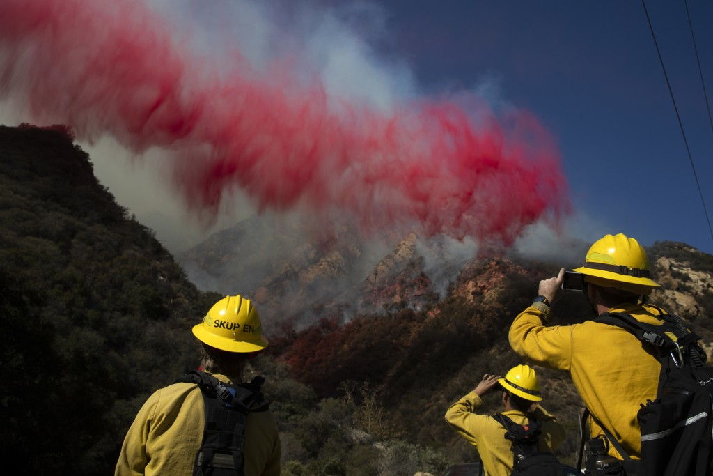FILE - In this Nov. 11, 2018 file photo firefighters take pictures of fire retardant dropped on a burning hillside in Malibu, Calif. A group of U.S. s