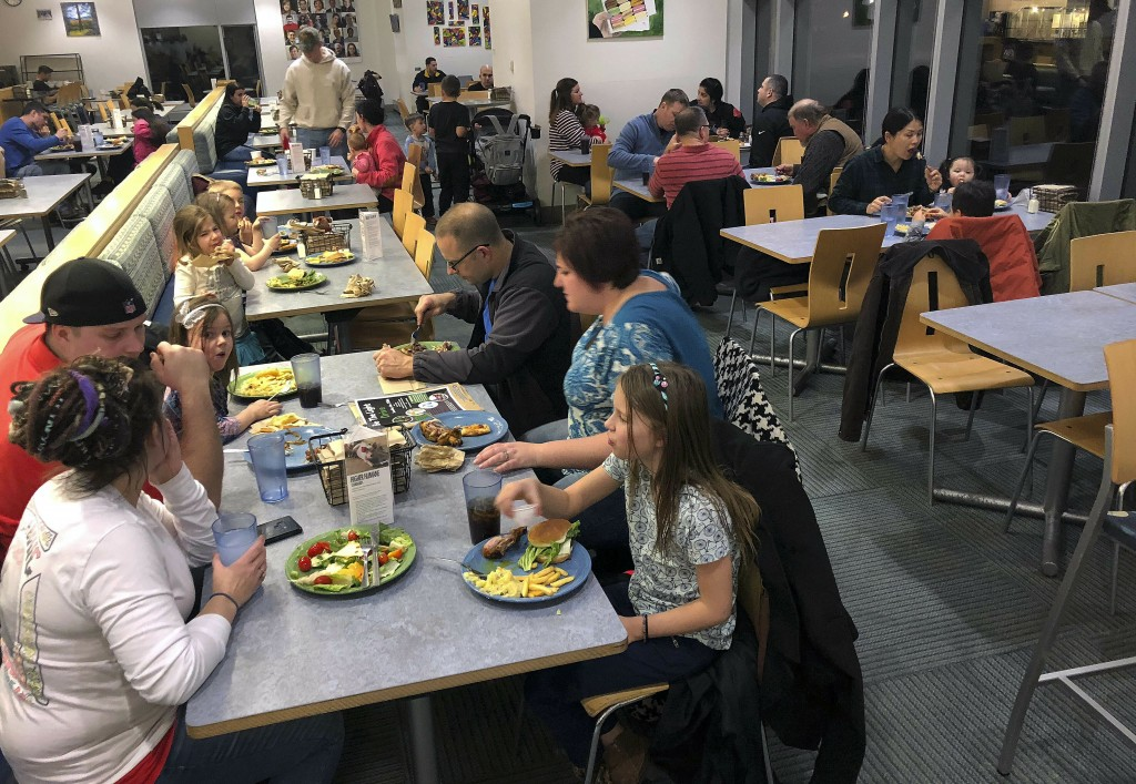 U.S. Coast Guard families enjoy dinner, Tuesday, Jan. 15, 2019, at Roger Williams University in Bristol, R.I. The college offered the free meal for ac