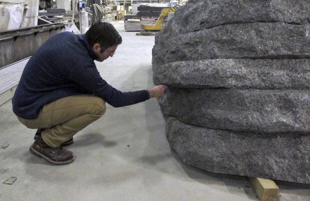 In this Tuesday, Jan. 8, 2019 photo, architect Michael Arad, a designer of the World Trade Center memorial, examines a granite monolith being created ...