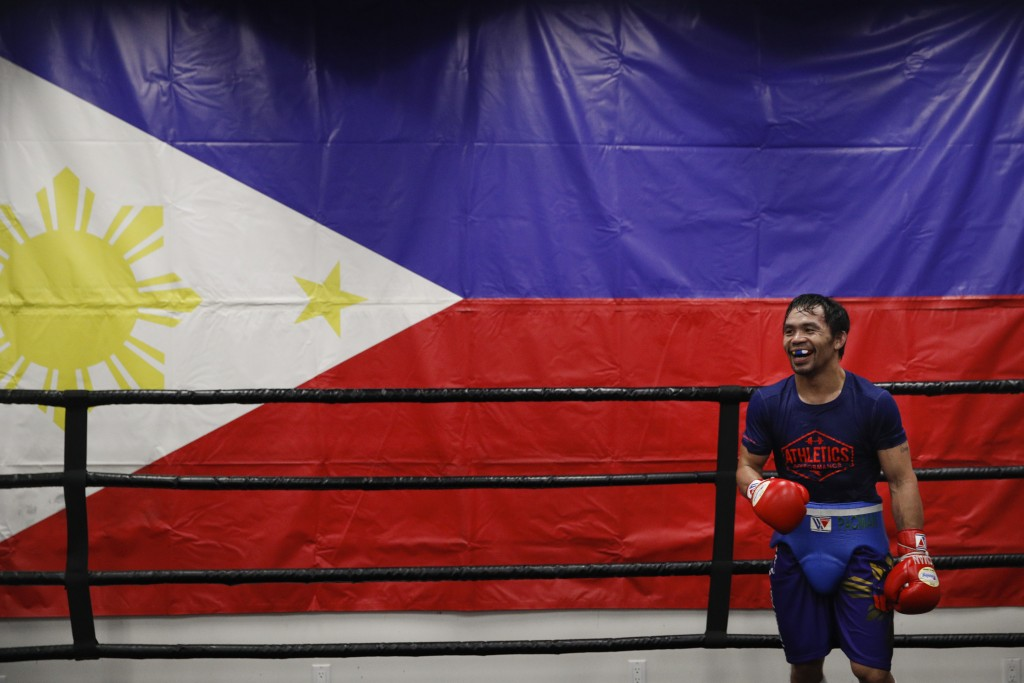 Standing in front of a large Filipino flag, boxer Manny Pacquiao smiles while training at the Wild Card Boxing Club Monday, Jan. 14, 2019, in Los Ange