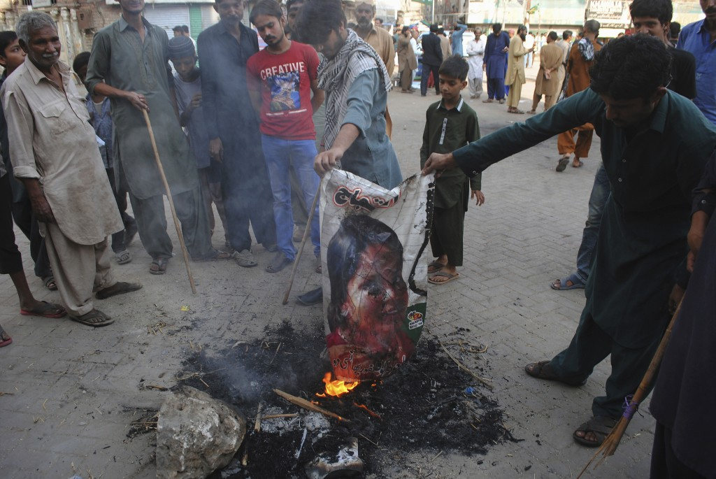 FILE - In this Nov. 1, 2018, file photo, Pakistani protesters burn a poster showing Aasia Bibi, in Hyderabad, Pakistan. In Mid January 2019, Bibi, a P