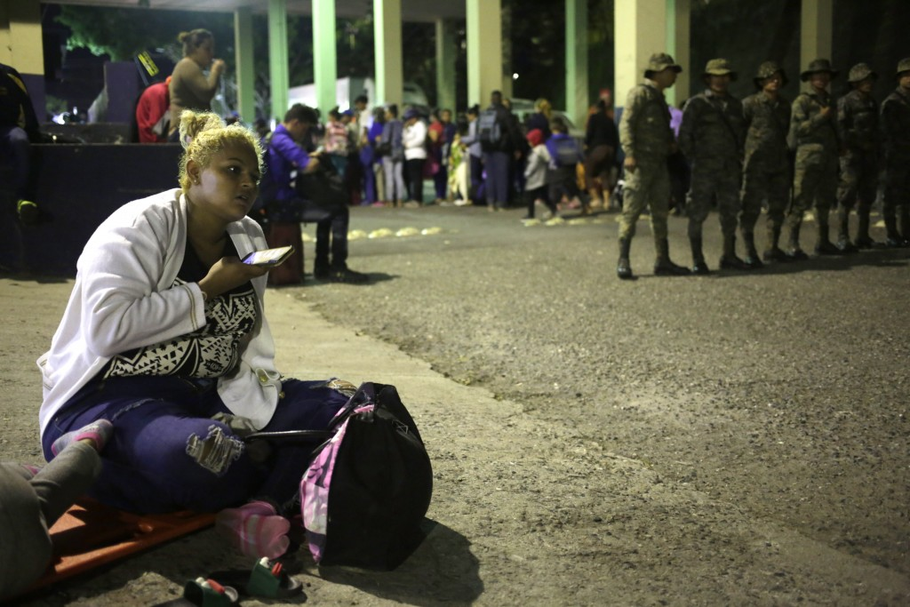 A Honduran migrant listens to her mobile phone while waiting to enter Guatemala, at the border crossing in Agua Caliente, Guatemala, Tuesday, Jan. 15,