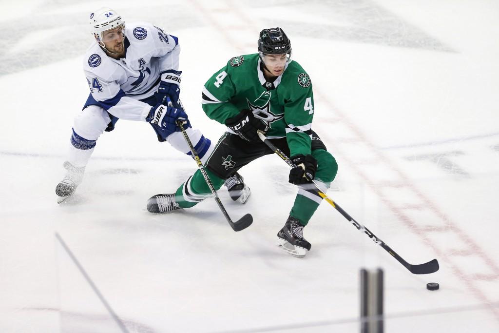 Tampa Bay Lightning forward Ryan Callahan (24) battles Dallas Stars defenseman Miro Heiskanen (4) for the puck during the first period of an NHL hocke...