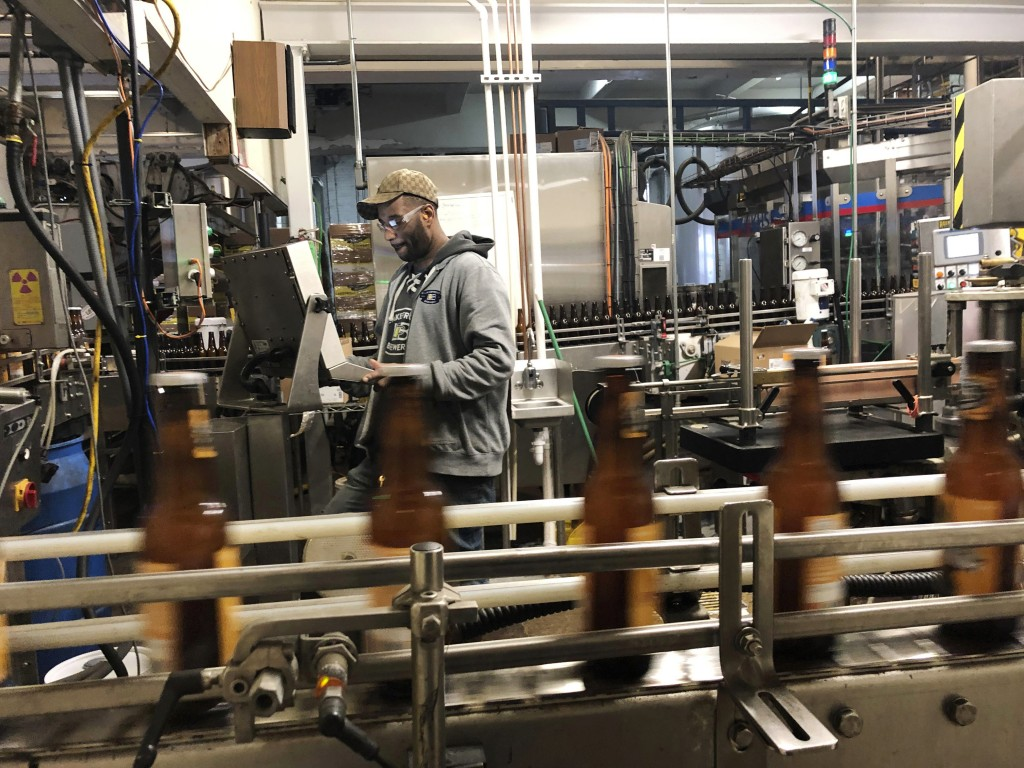 In this Jan. 14, 2019, photo, Trevor Stevens works in the bottling room at Lakefront Brewery in Milwaukee. The federal shutdown is impacting the feder...