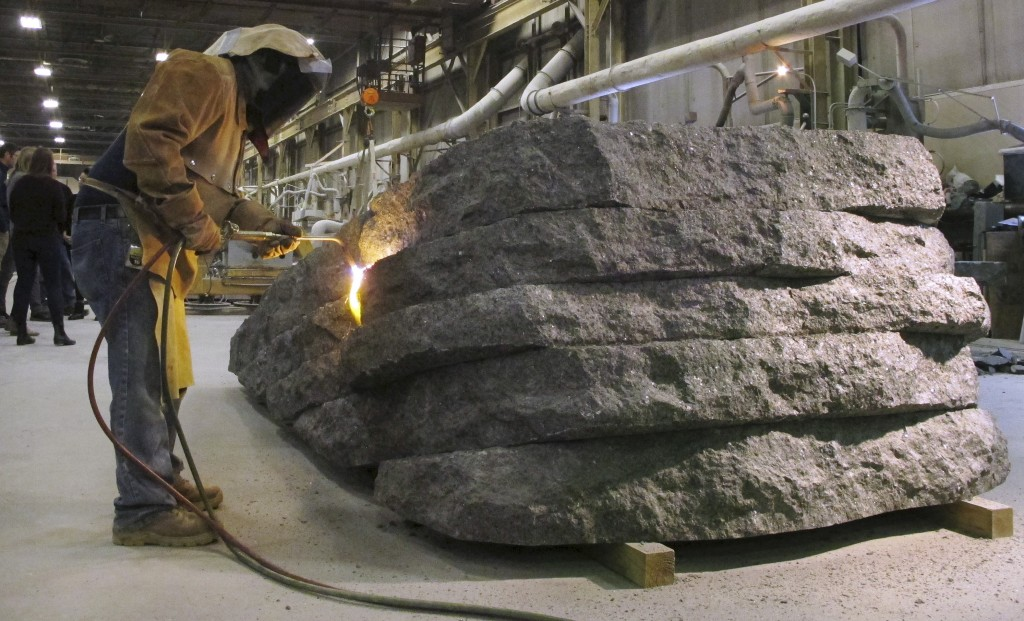 In this Tuesday, Jan. 8, 2019 photo, a worker uses a torch to finish a granite monolith at Rock of Ages in Barre, Vt. The monolith will be one of six ...