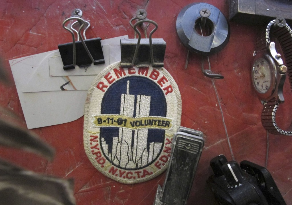 In this Tuesday, Jan. 8, 2019 photo, a badge remembering the Sept. 11, 2001, terrorists attacks hangs in the work area of a stone cutter at Rock of Ag...