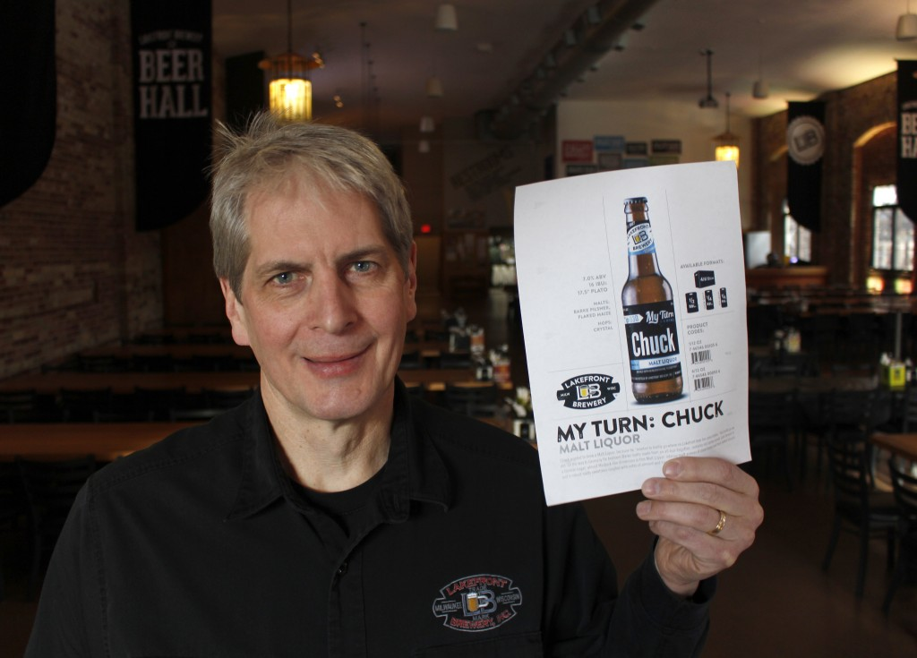 """In this Jan. 11, 2019, photo, Russ Klisch, founder and president of Lakefront Brewery, holds up a photo of """"My Turn: Chuck"""" beer. The federal shutdown..."""