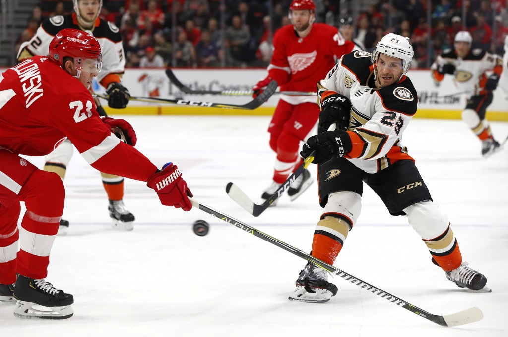 Anaheim Ducks center Brian Gibbons (23) shoots over Detroit Red Wings defenseman Dennis Cholowski (21) in the first period of an NHL hockey game, Tues