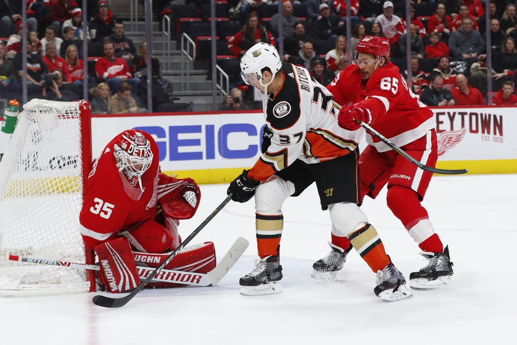 Detroit Red Wings goaltender Jimmy Howard (35) stops a shot by Anaheim Ducks left wing Nick Ritchie (37) as defenseman Danny DeKeyser (65) defends in ...