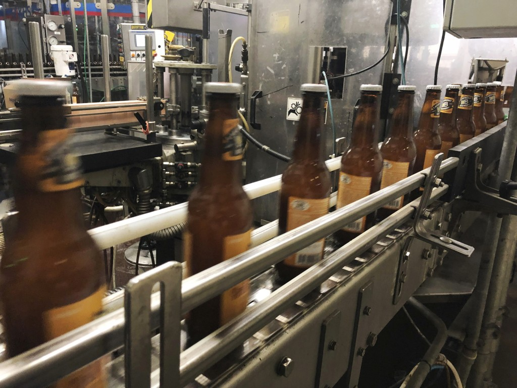 In this Jan. 14, 2019, photo, bottles, freshly filled with beer, move on a belt at Lakefront Brewery in Milwaukee. The federal shutdown is impacting t...