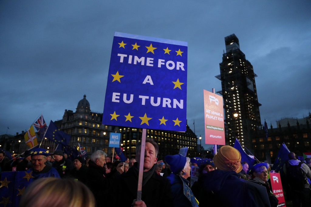 Pro-European demonstrators hold posters at Parliament Square in London, Tuesday, Jan. 15, 2019. Britain's Prime Minister Theresa May is struggling to ...