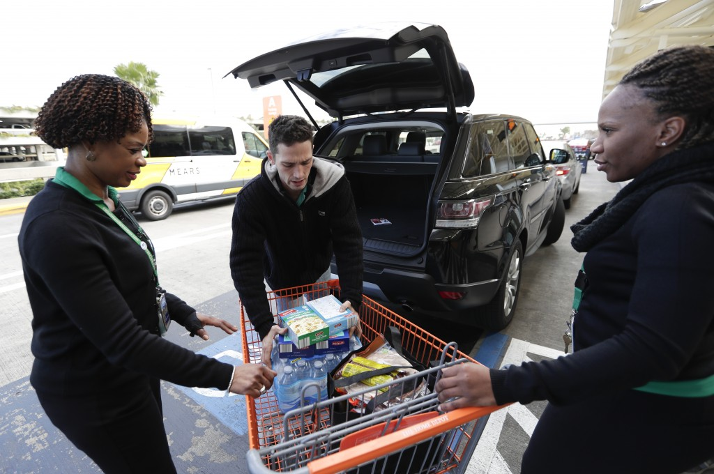 Frontier Airlines employees Nickeda McPhee-Gomez, left, and Antonine Maricel, right, collect donations of food and supplies to be given to TSA workers