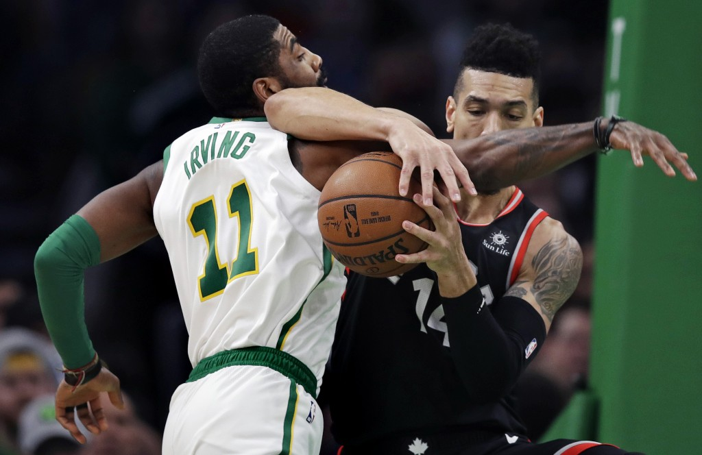 Boston Celtics guard Kyrie Irving (11) and Toronto Raptors guard Danny Green, right, tangle as they compete for the ball during the first quarter of a