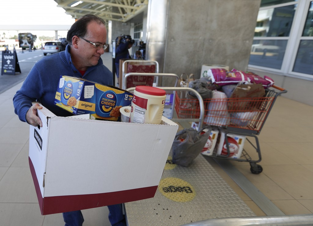 Erwin Guzman drops a food and supply donation for TAS workers at Orlando International Airport Wednesday, Jan. 16, 2019, in Orlando, Fla.  as the part